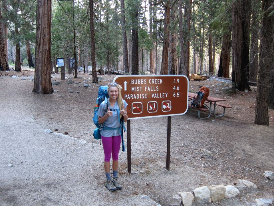 Girl in front of the starting sign to the Rae Lakes Loop trail