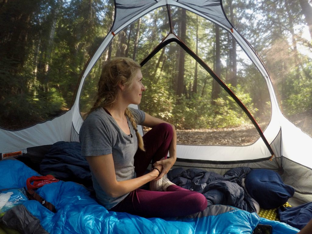 Girl sitting in tent with views of the trees