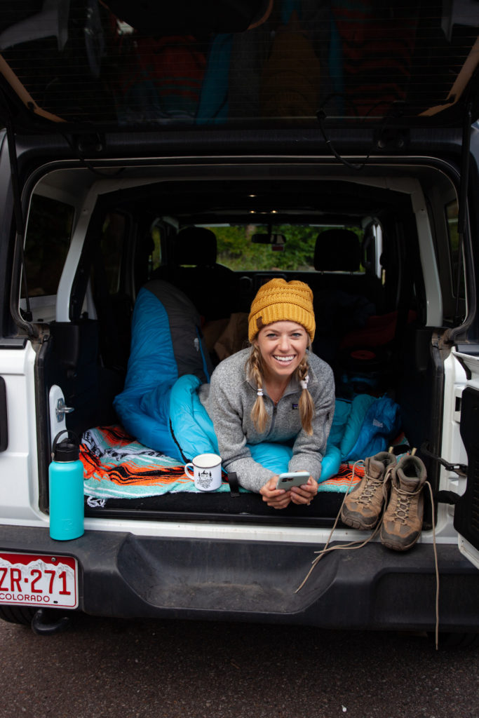 Girl in the back of a Jeep about to go to bed because she found a free camping spot in the US