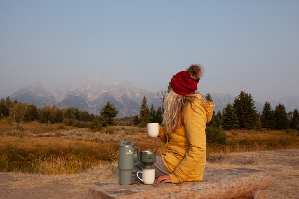 Chelsey in front of the Grand Tetons with her Stanley pour over coffee maker