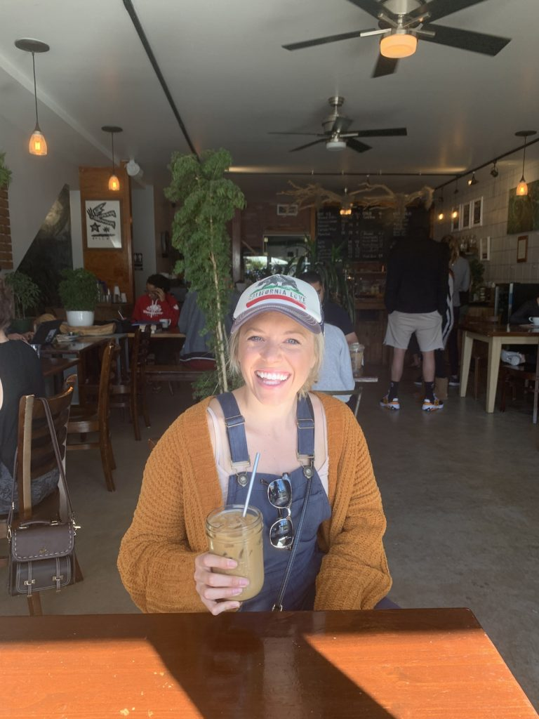 Chelsey holding a coffee at Bay Park Coffee in San Diego