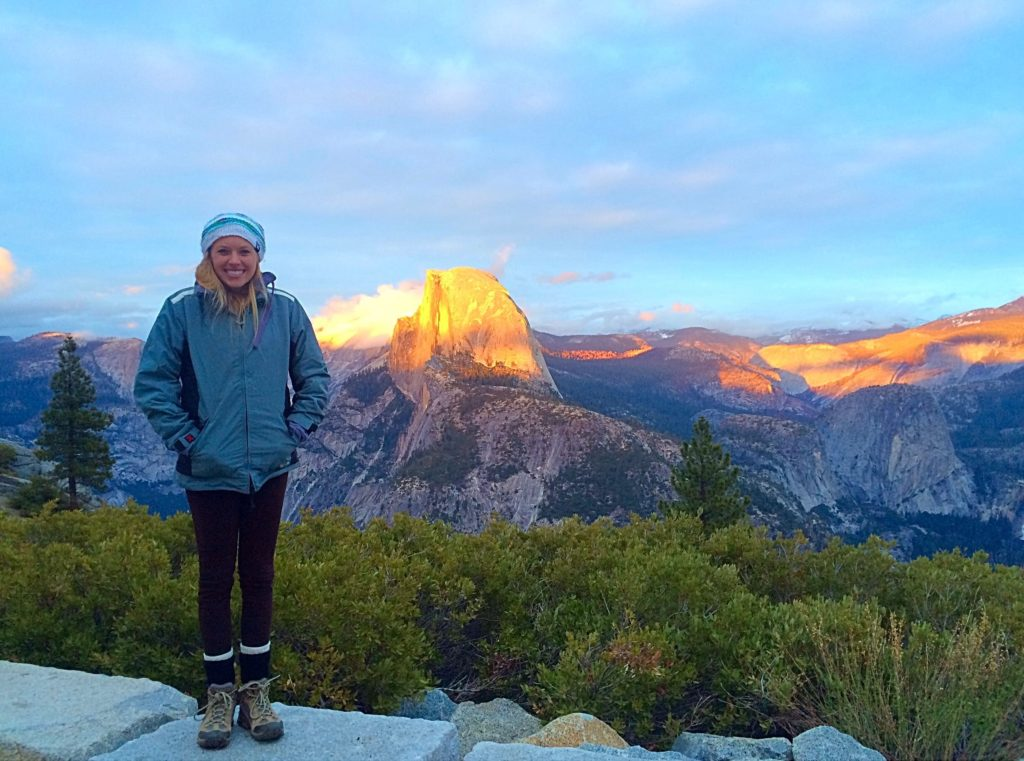 Yosemite National Park offers some of the best hikes near San Francisco. Here is a girl standing in front of halfdome at sunrise