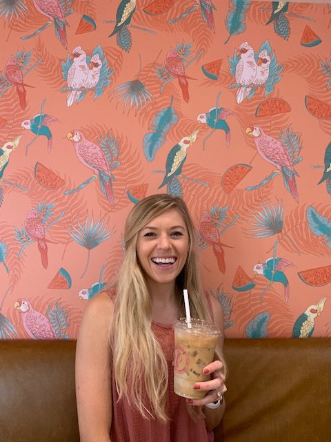Chelsey holding coffee in front of a Parakeet wall at Parakeet cafe: one of the cutest coffee shops in San Diego