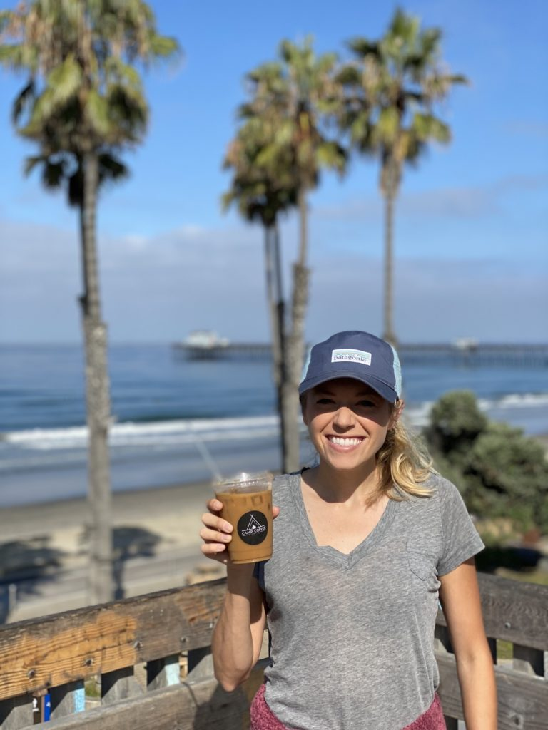 Girl holding iced coffee on the beach with palm trees in the background