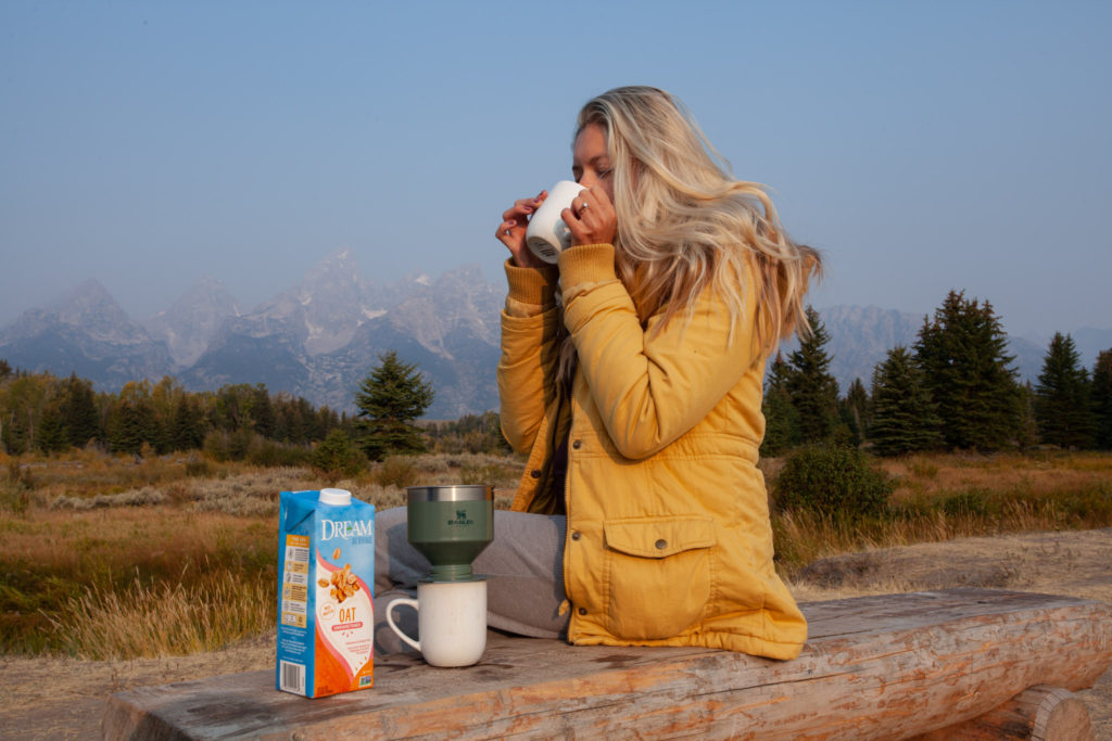 Girl drinking coffee in front of the Grand Tetons
