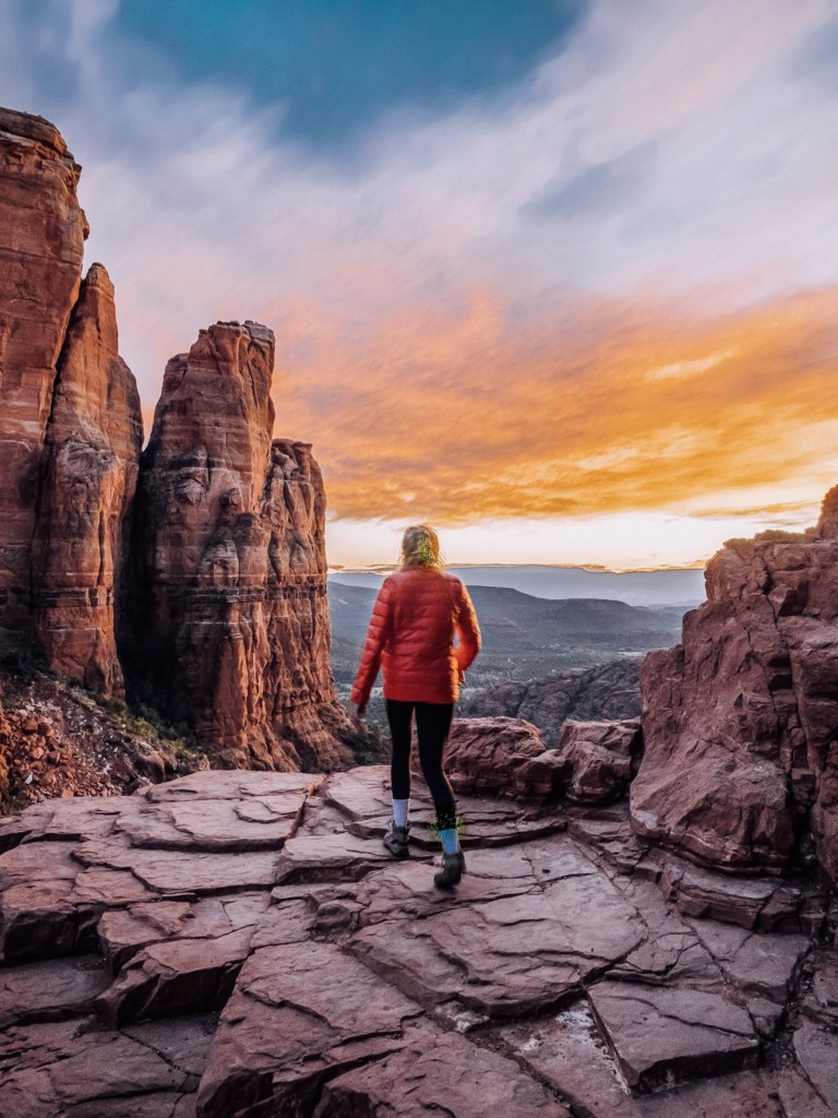 Girl at the top of Cathedral Rock hike in Sedona with a sunset in the background