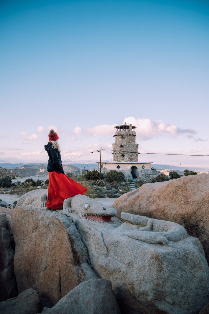 Girl in skirt standing on boulder park rocks with view of the desert view tower in the background