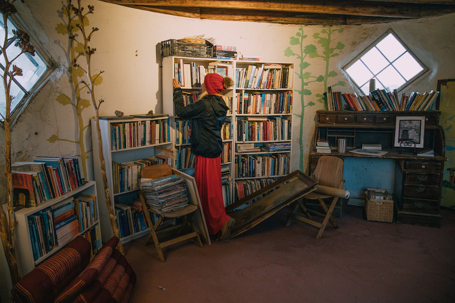 Girl looking through the bookshelf inside the desert view tower