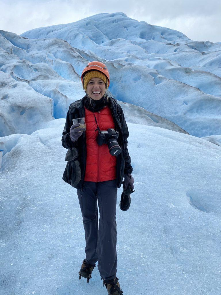 Girl holding a whiskey drink on the Perito Moreno Glacier