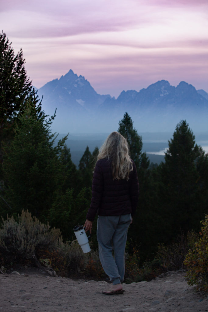 Girl standing in front of the grand Tetons with her water bottle which is an essential item for camping