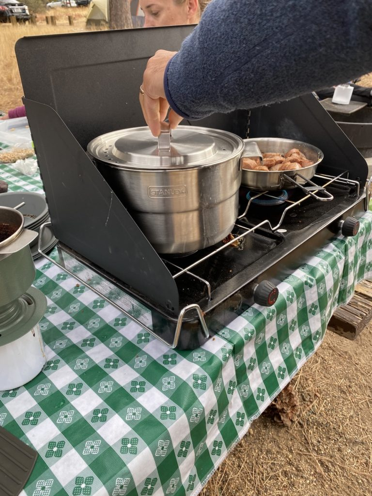 Cooking on a camp stove which is essential for camping