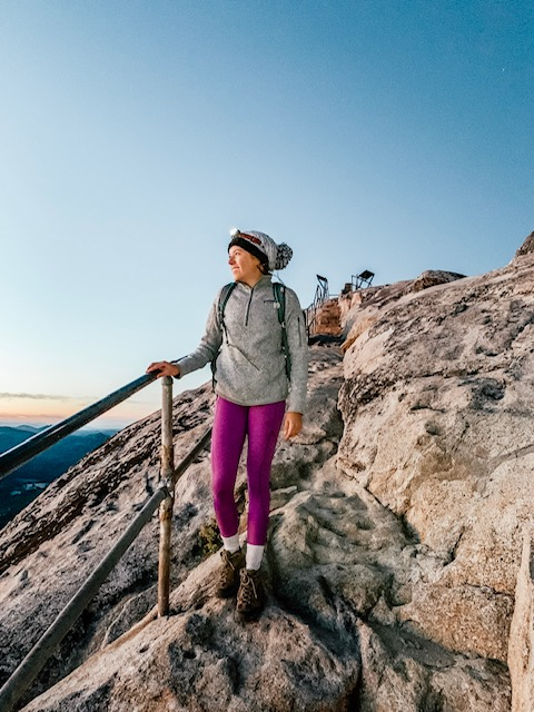 Girl hiking with a headlamp on her head as a headlamp is an essential camping gear item