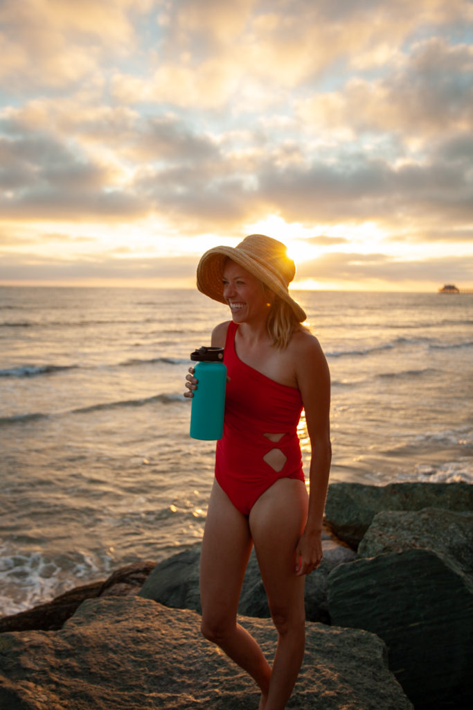 Girl on Oceanside beach with the sunset behind her
