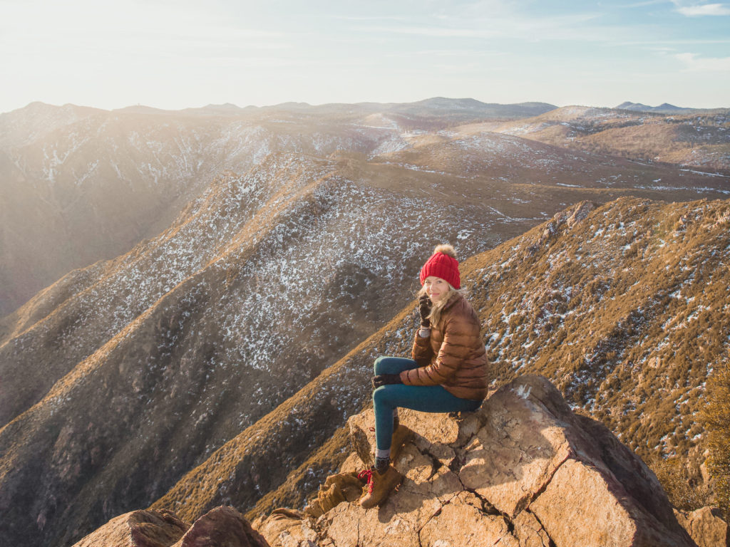 Girl sitting on the mountain in her hiking boots