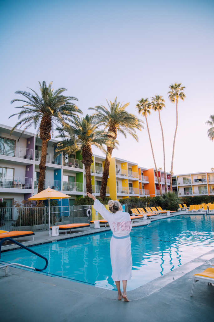 Girl standing in front of the pool at the Saguaro which is a hotel to stay at on your Palm Springs weekend getaway